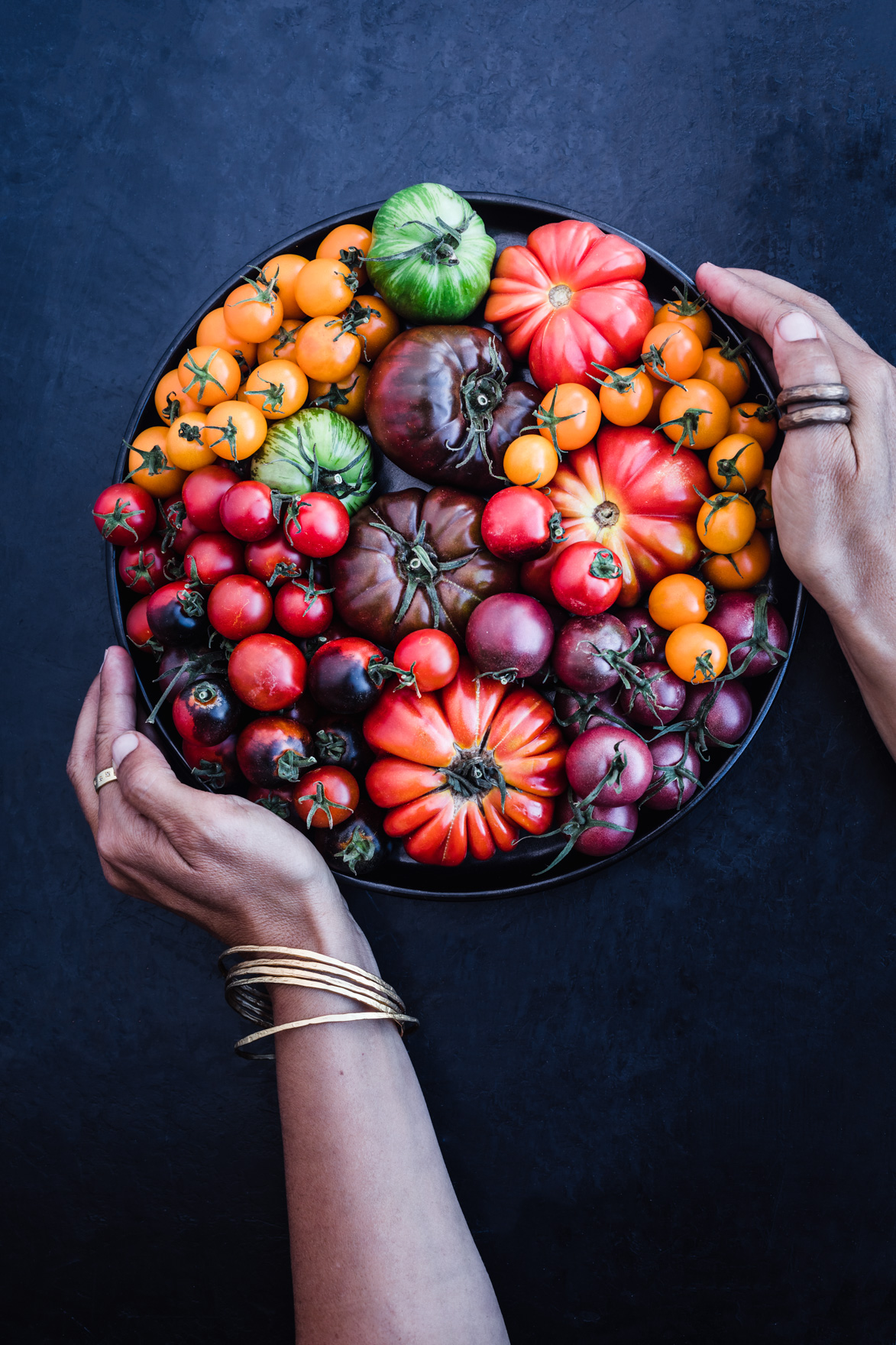 Chef Daniela Gerson holding fresh summer tomatoes on a black plate.