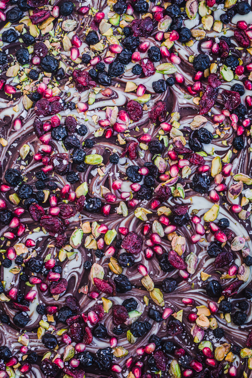 Dark chocolate bark with pistachios, dried cherries, dried cranberries, pomegranate seeds, flaky sea salt and a white chocolate swirl on top.