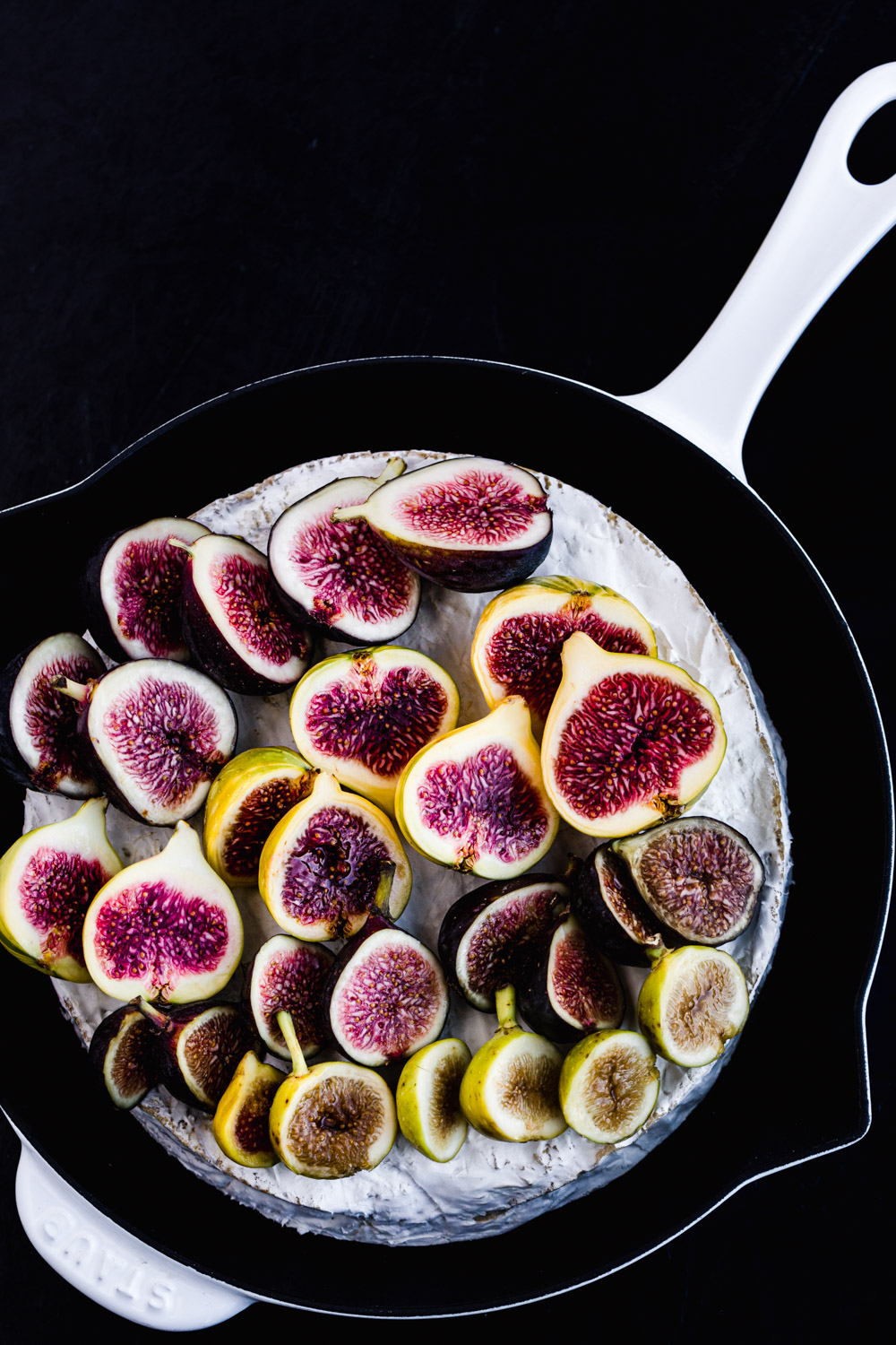 Brie in a baking dish with figs cut in half on top.