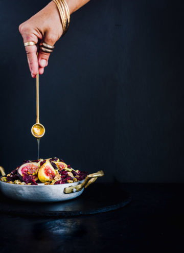 Chef Daniela Gerson drizzling honey on a small baked brie topped with figs, nuts and dried cranberries.