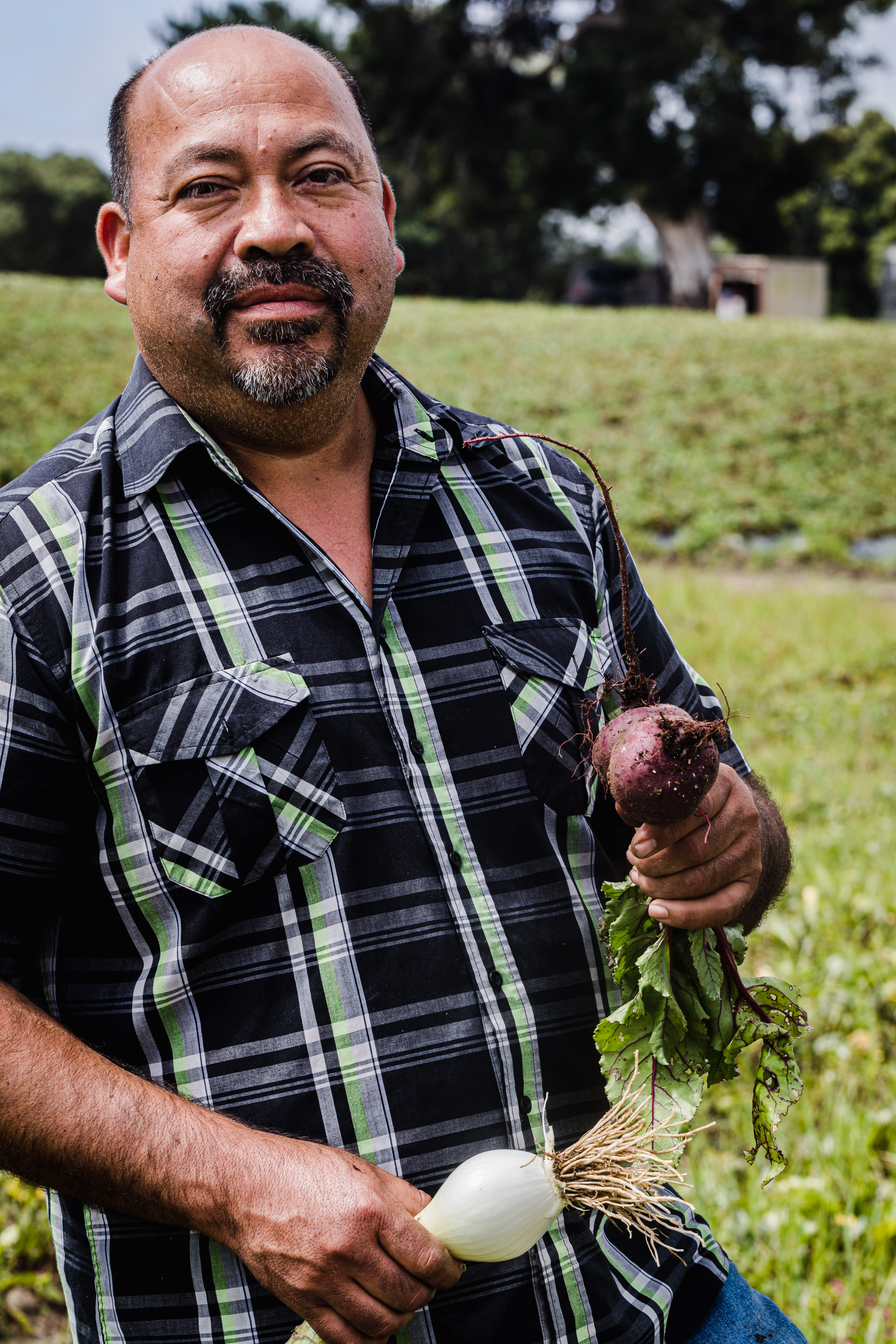 Javier Zamora, of JSM Organics, proudly standing with a freshly harvested beet and onion.