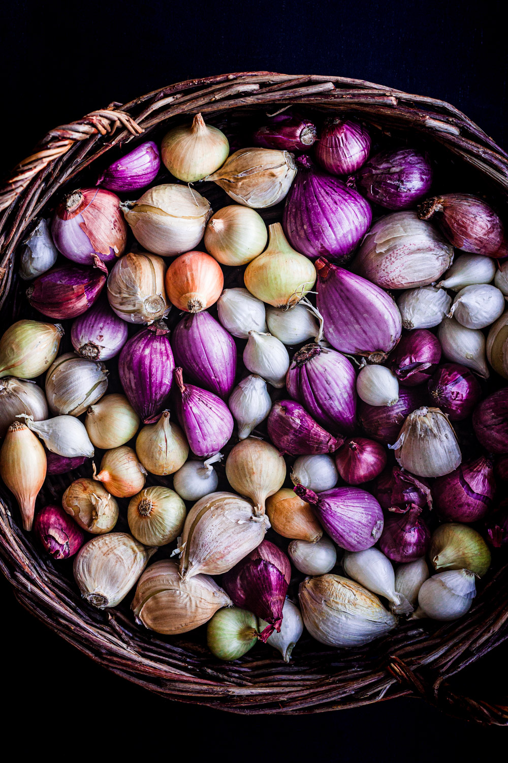 Ingredient shot of all different colors of shallots in a basket, overhear shot.