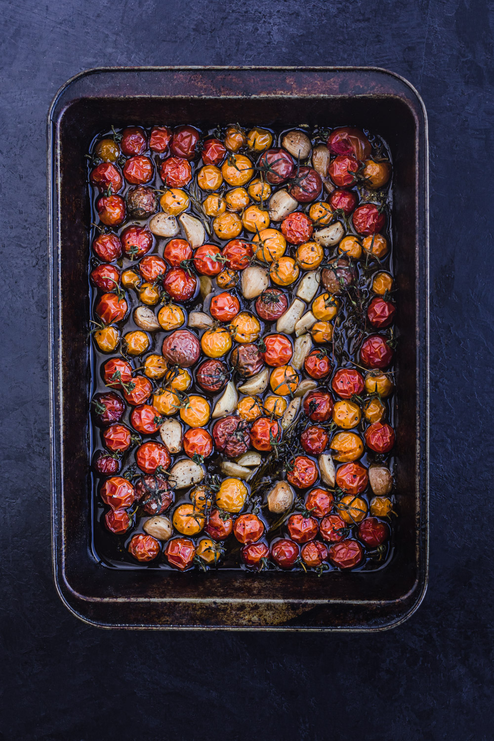 Cherry tomato confit, freshly out of the oven, on a tray, overhead shot on a black background.