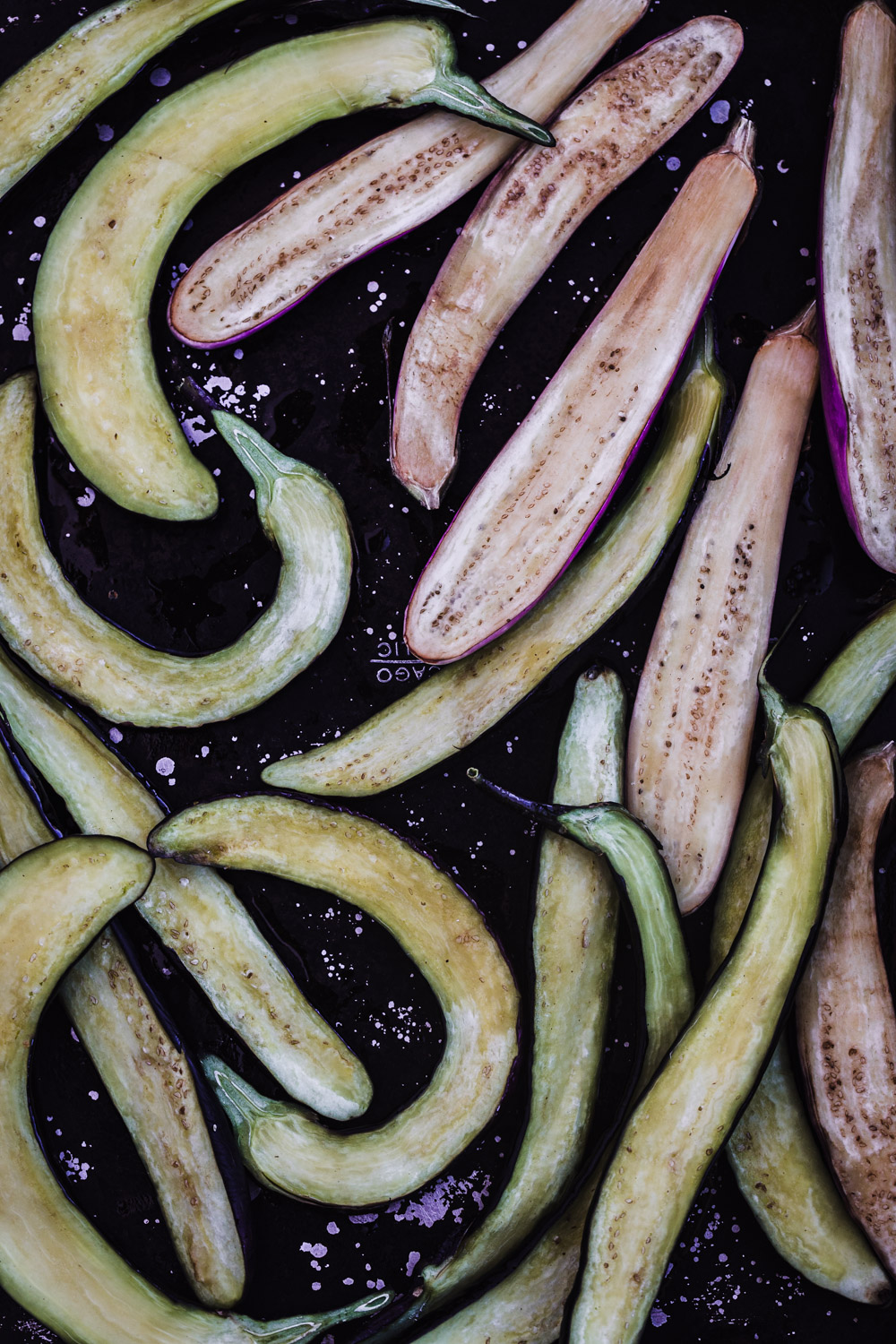 Japanese eggplant sliced in half lengthwise and coated with sesame oil.