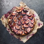 Plum, Walnut and Lavender Cake! Overhead shot on a black background.