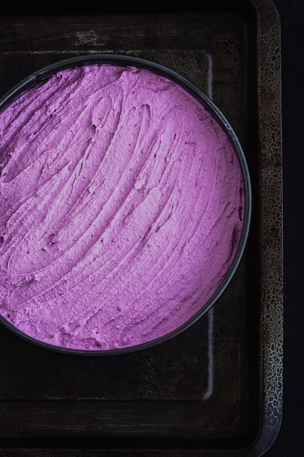 Purple sweet potato cheesecake batter, spread out on a spring foam pan.