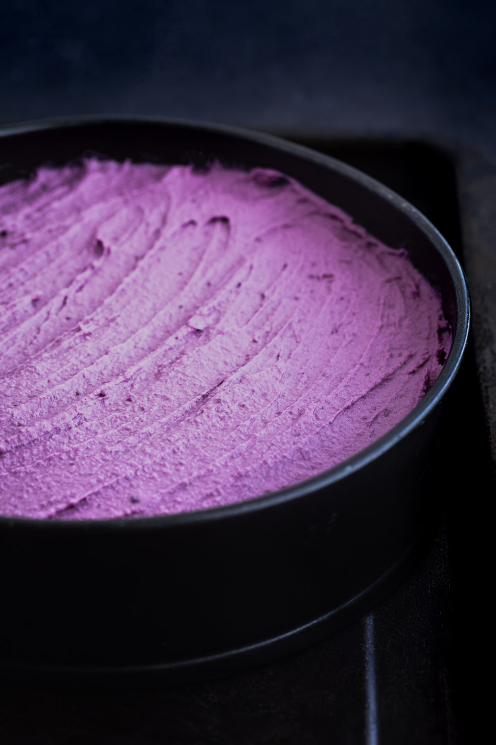 Side angle shot of the purple sweet potato cheesecake batter spread out on the spring foam pan.