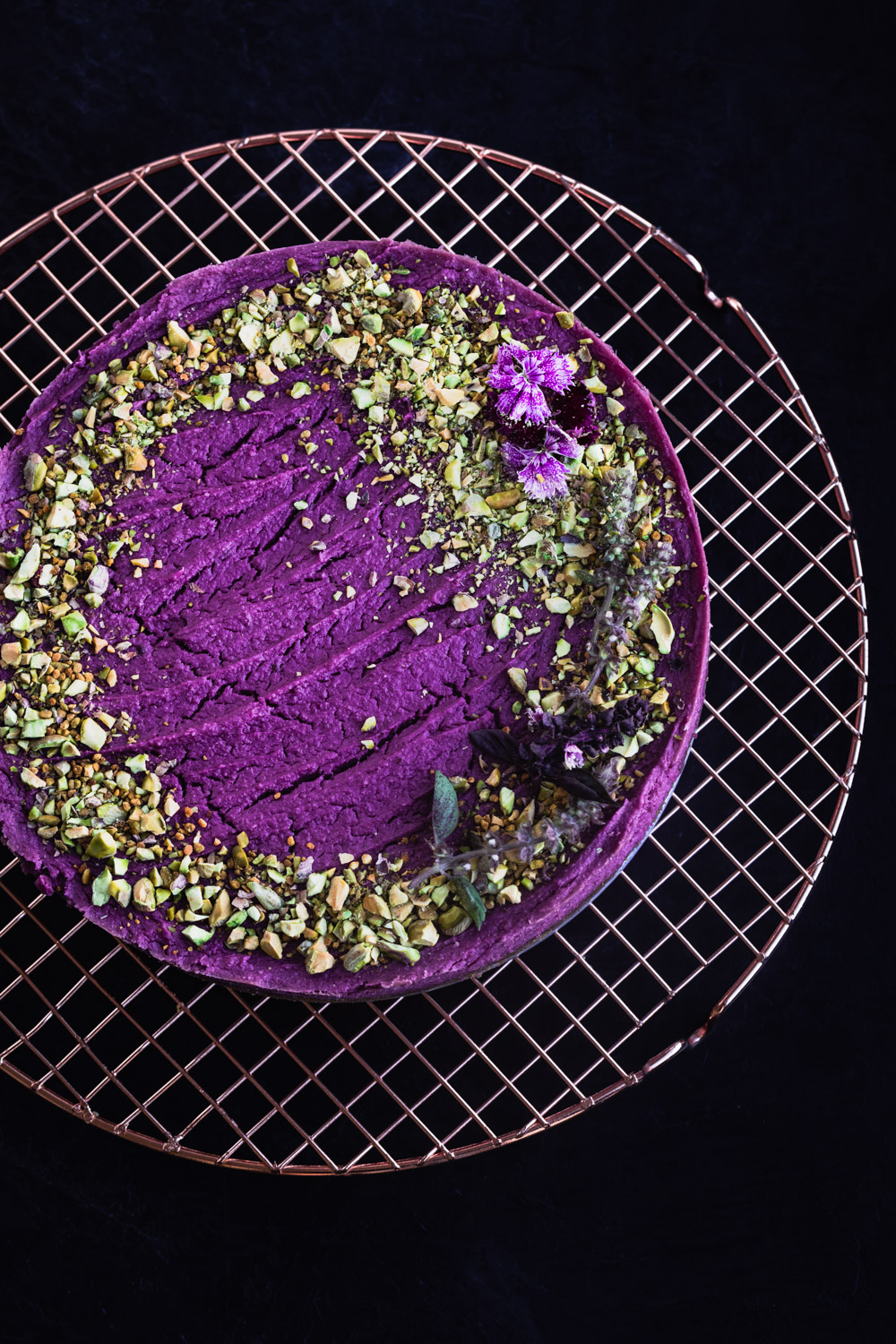 Purple sweet potato cheesecake topped with pistachios and edible flowers.