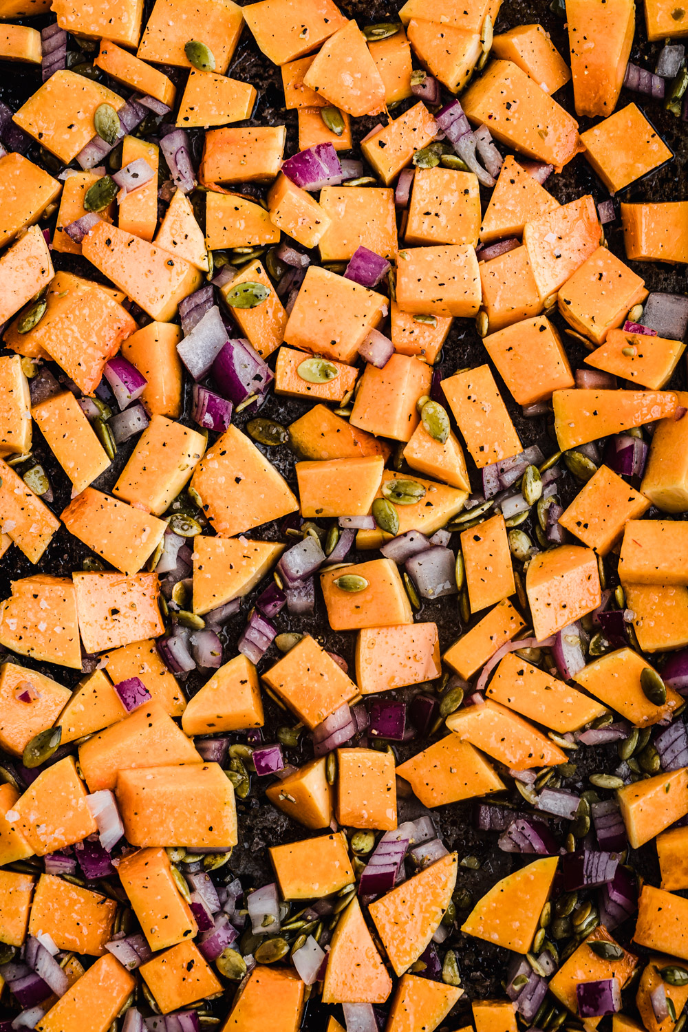 Cubed orange sweet potatoes with chopped onions and pepitas on a baking sheet, ready to be roasted.