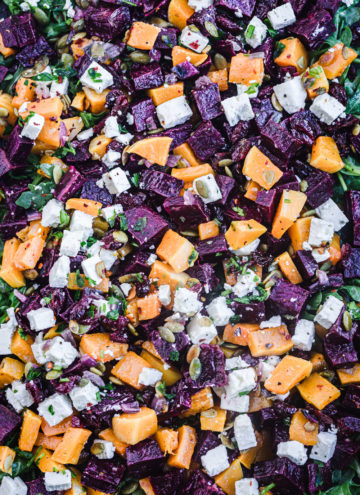 Sweet potato salad with argulula, feta, dried cranberries, red onions, pepitas, parsley and a maple-lime vinaigrette, overhead shot.