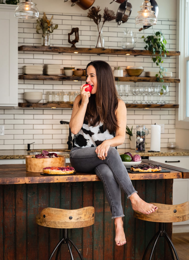 Chef Daniela Gerson eating an apple in the kitchen.