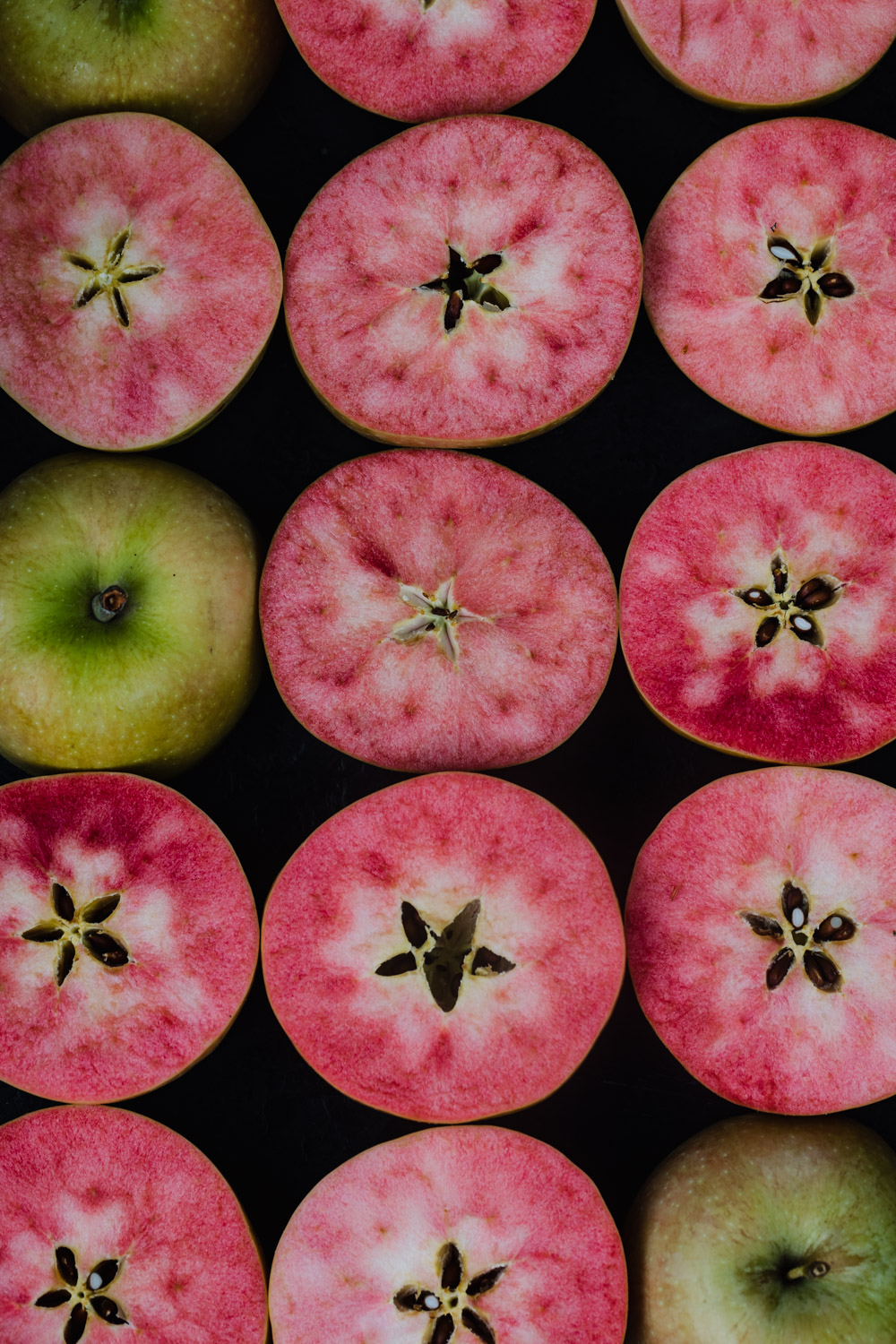 Pink hidden rose apples, cut in half to reveal their pink insides, overhead shot.