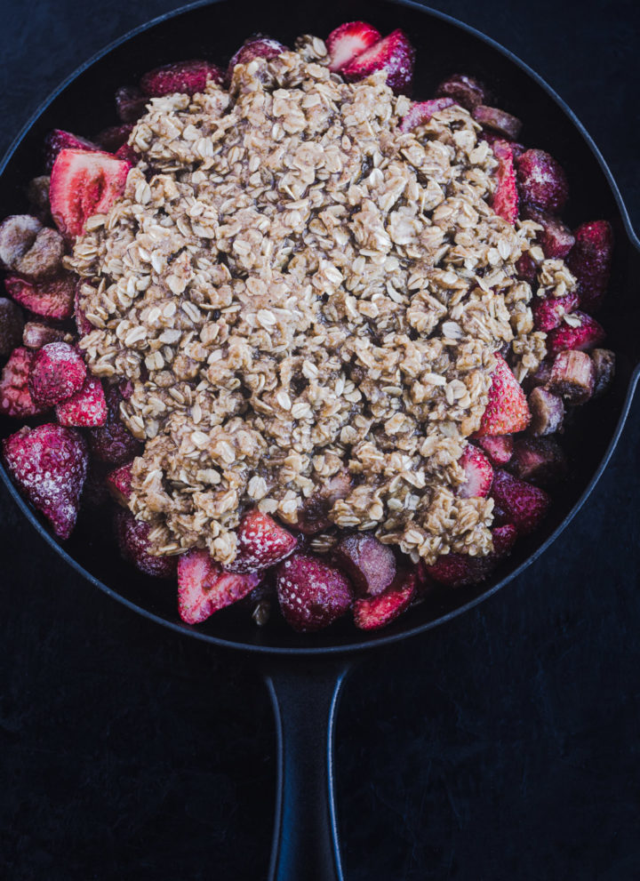 Strawberry-Rhubarb crisp in a cast iron skillet with the oat topping, ready for the oven, overhead shot.