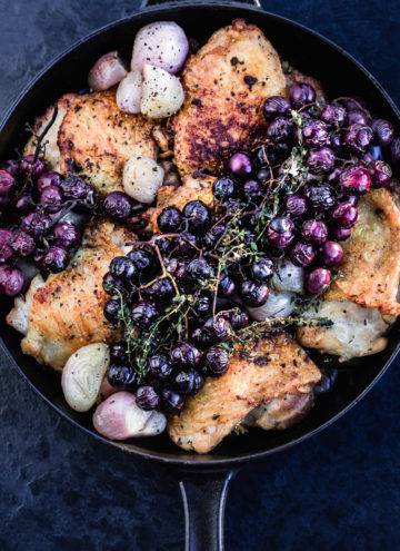 Close up shot of the finished thyme roasted chicken with shallots and grapes, in a cast iron skillet.