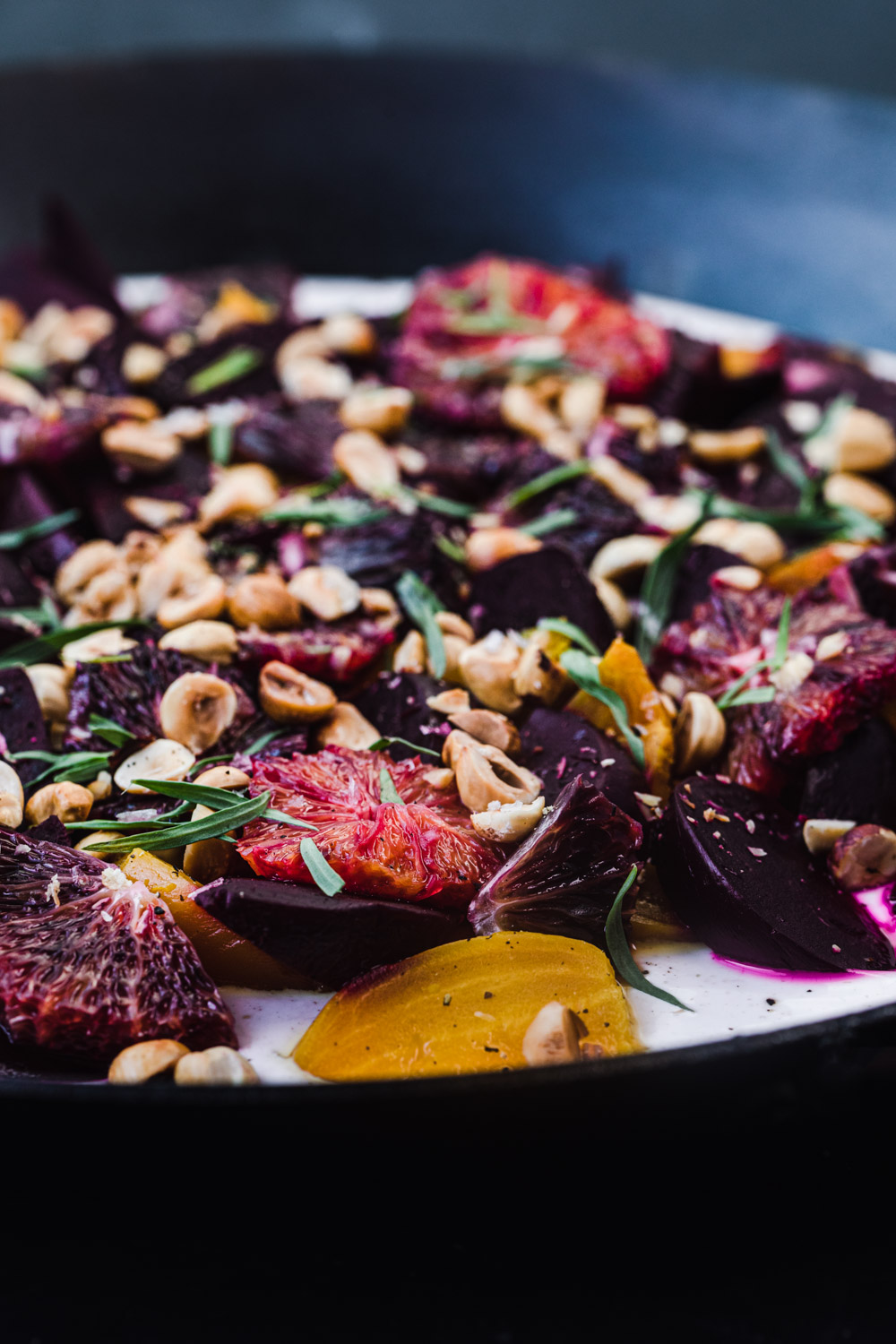 Up close shot of roasted beet salad with blood oranges, on yogurt.