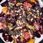 Overhead shot of the final roasted beet salad with yogurt, blood oranges, hazelnuts, and tarragon.