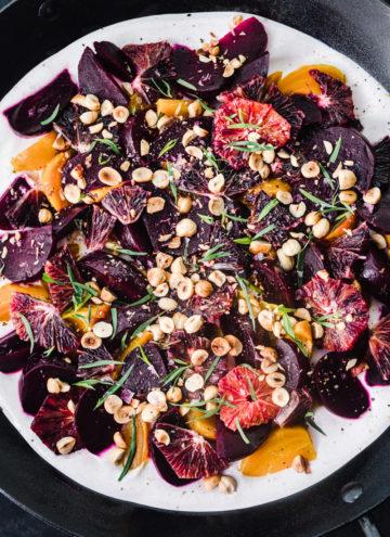 Overhead shot of the final roasted beet salad with yogurt, blood oranges, hazelnuts, and tarragon.