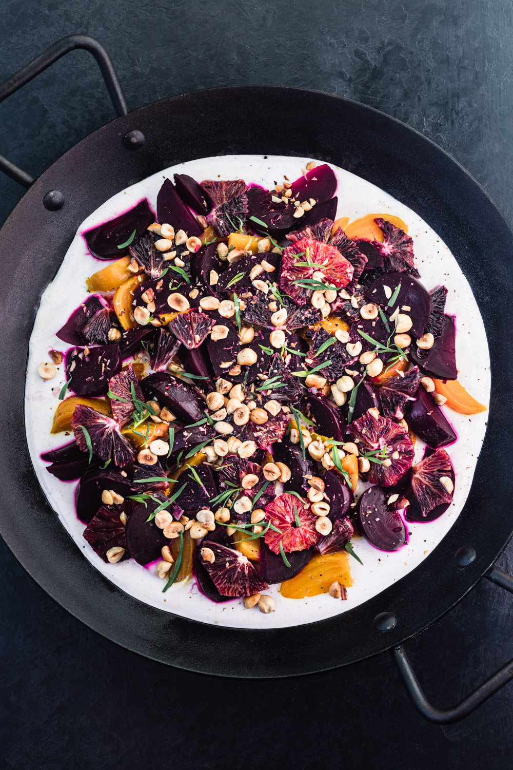 Roasted Beet Salad on a big black serving tray, on a black background, with all the toppings and ready to be eaten.