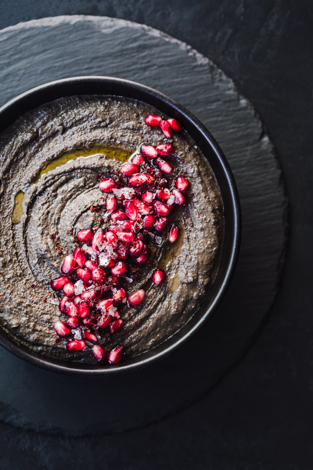 black hummus with pomegranate arils, flaky sea salt, sumac and olive oil