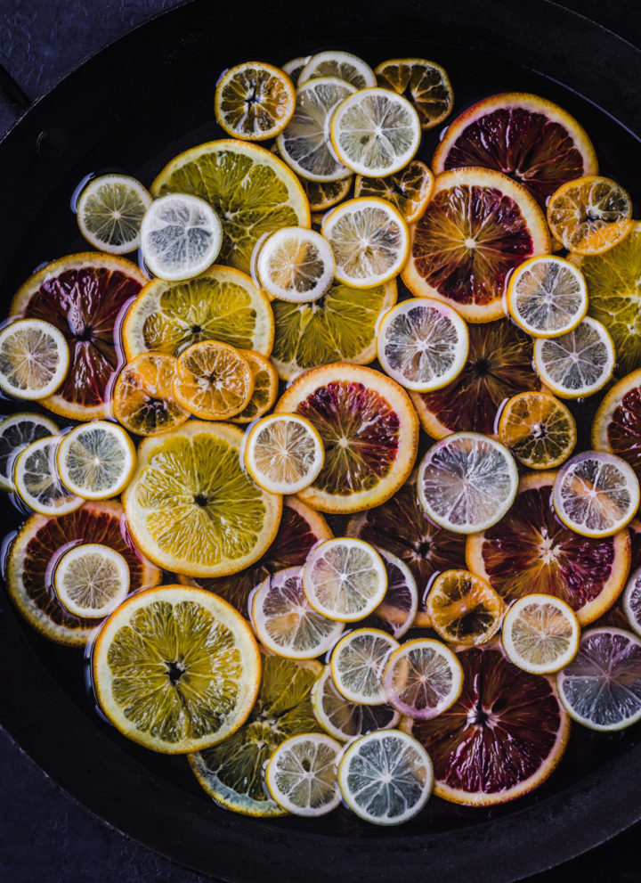 An assortment of citrus simmering in simple syrup. In process shot of citrus being candied!