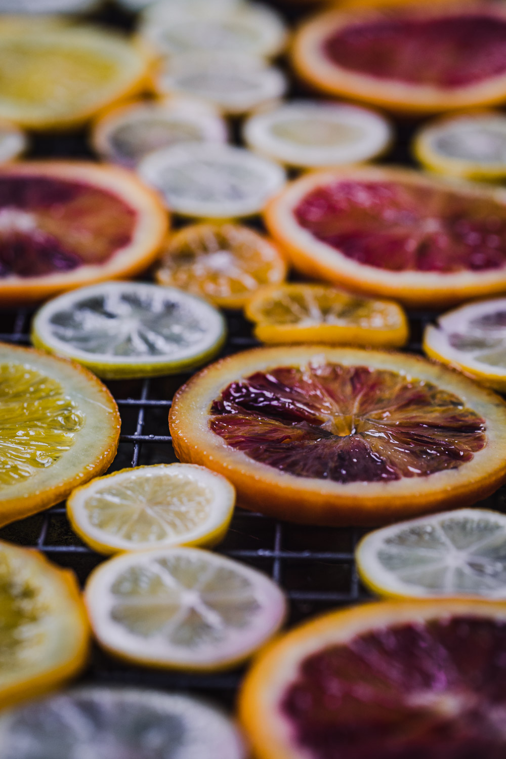 Up close shot of colorful citrus drying on a wire rack, side angle shot.