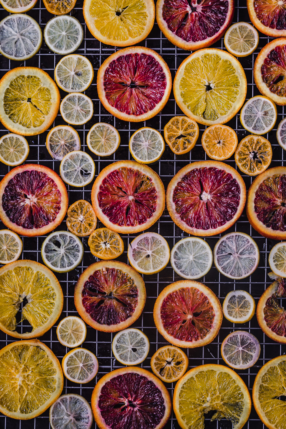 Overhead shot of an assortment of citrus types drying on a rack.