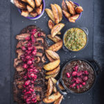 Thinly sliced brisket on a black slate with cranberry sauce on top, baked wedge potatoes and 2 little bowls of chimichurri and more cranberry sauce.
