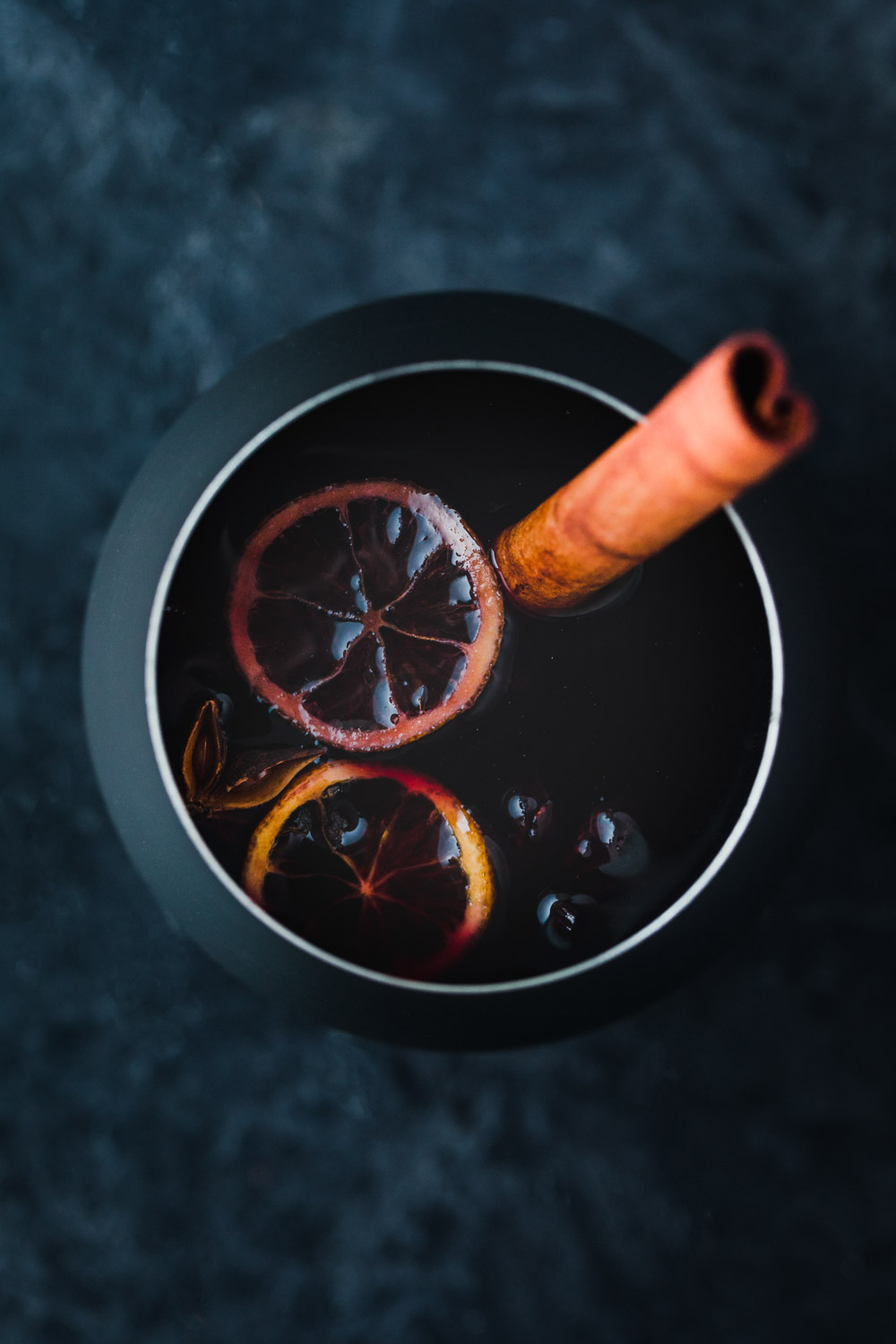 spiced wine poured into a black mug with a cinnamon stick, star anise, cloves, and sliced citrus.