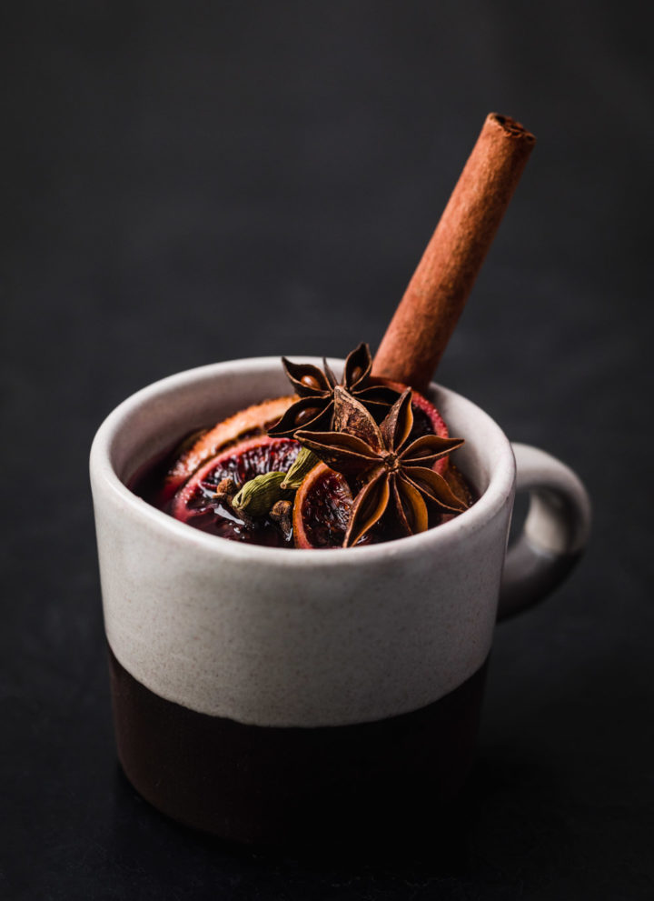 Side angle shot of spiced wine with a few star anise, cardamom pods, blood orange and cloves.