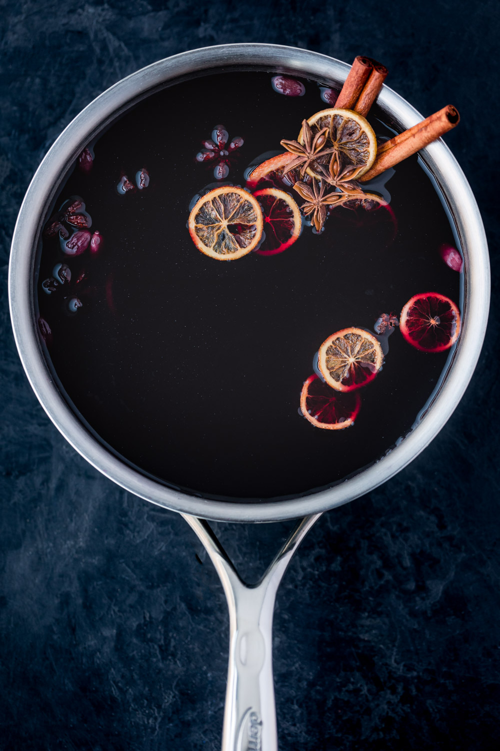 In process shot of spiced wine simmering in saucepan with all the spices, sugar, and citrus.