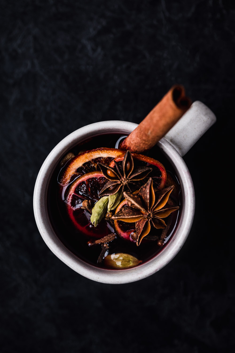 Overhead shot of spiced wine with a few star anise, cardamom pods, blood orange and cloves.