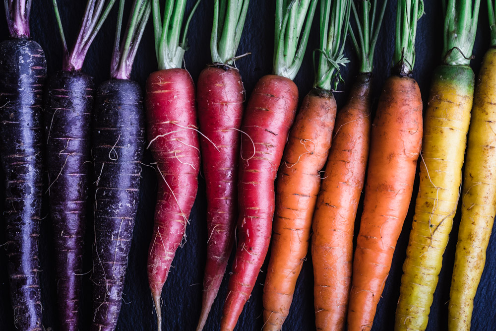 ingredient shot of rainbow carrots! unpeeled and whole, purple, coral, orange and yellow
