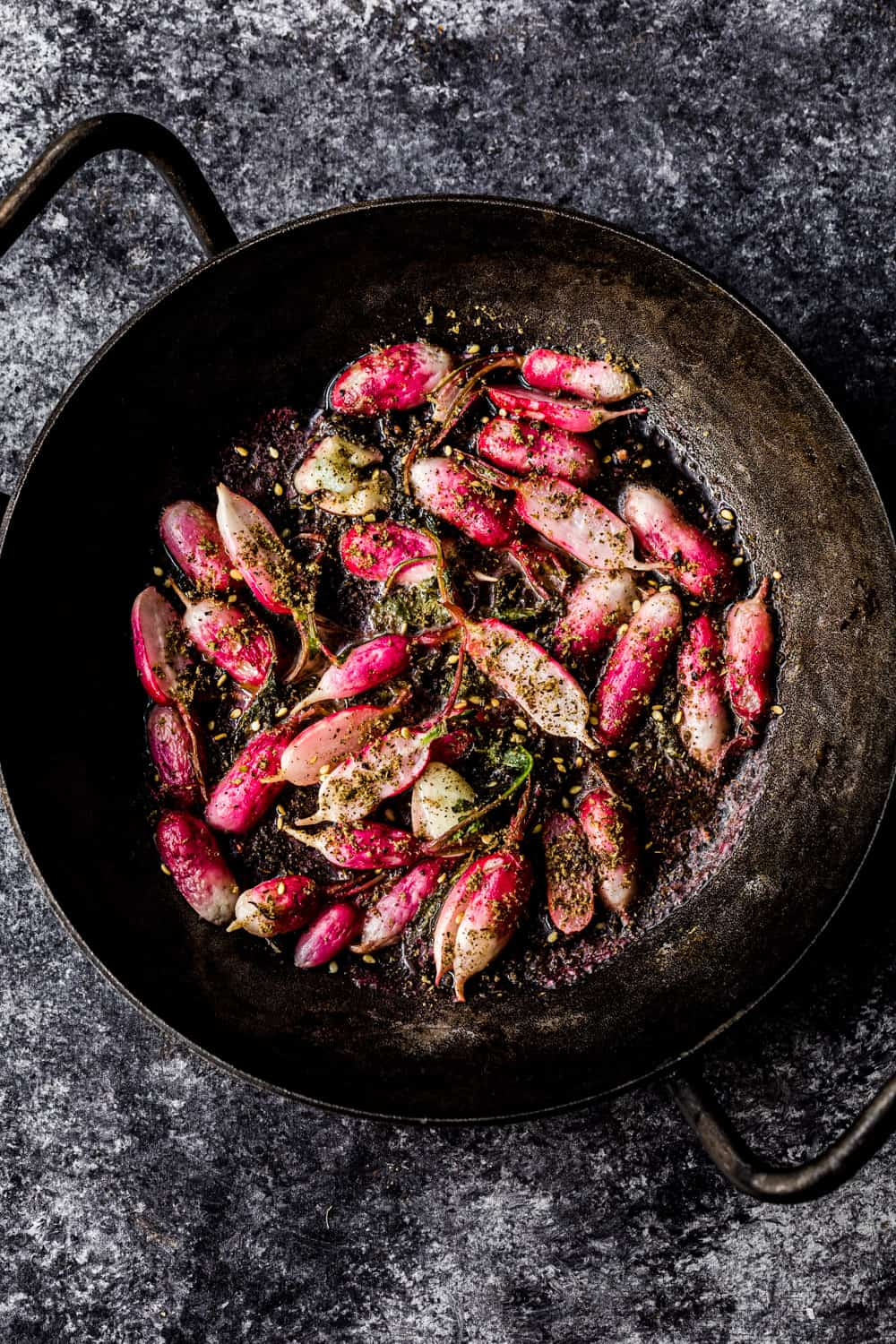 sauteed radishes in a skillet with za'atar, overhead shot to be used in the farmers market salad
