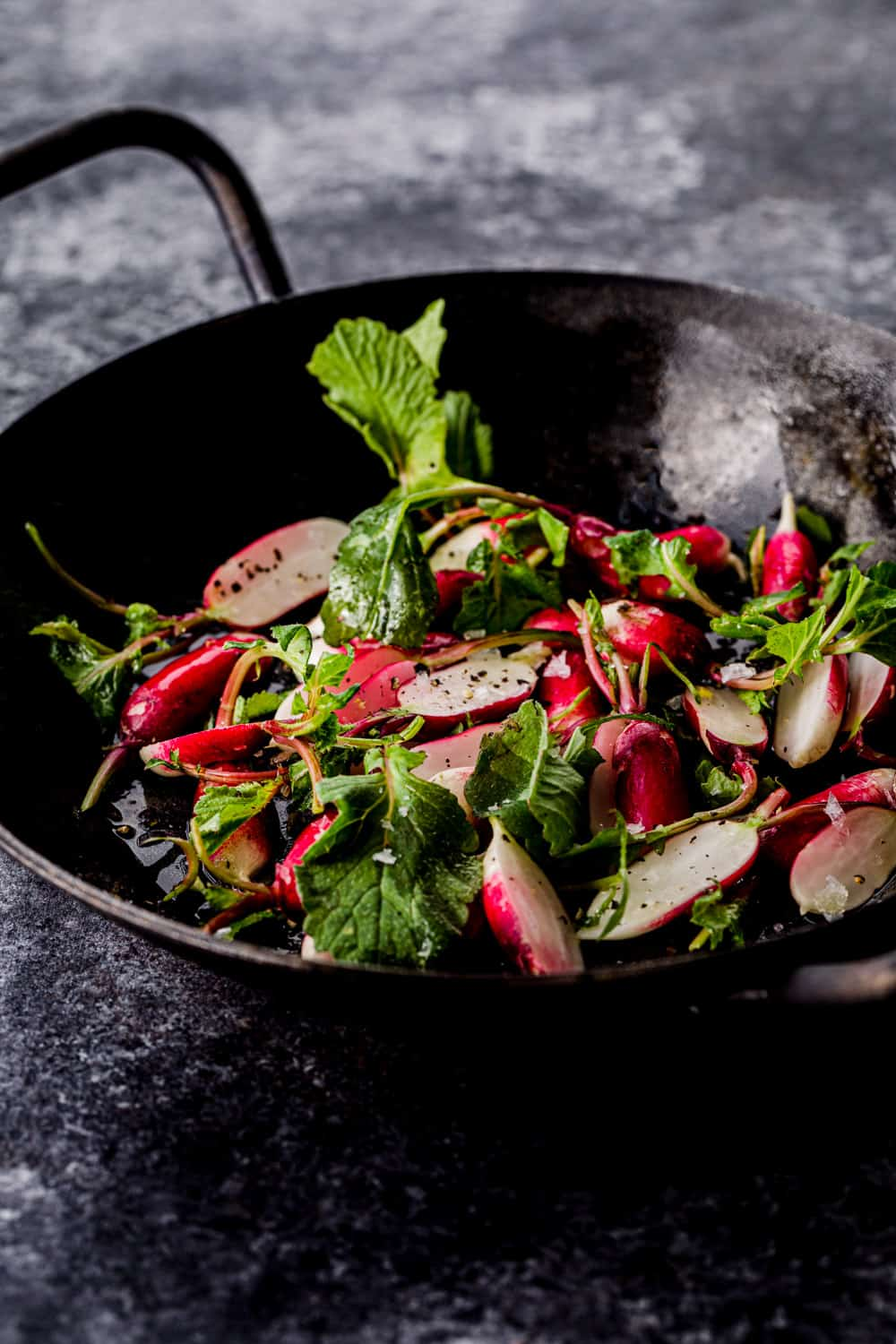 side angle shot of raw radishes in a little skillet to be used in the farmers market salad