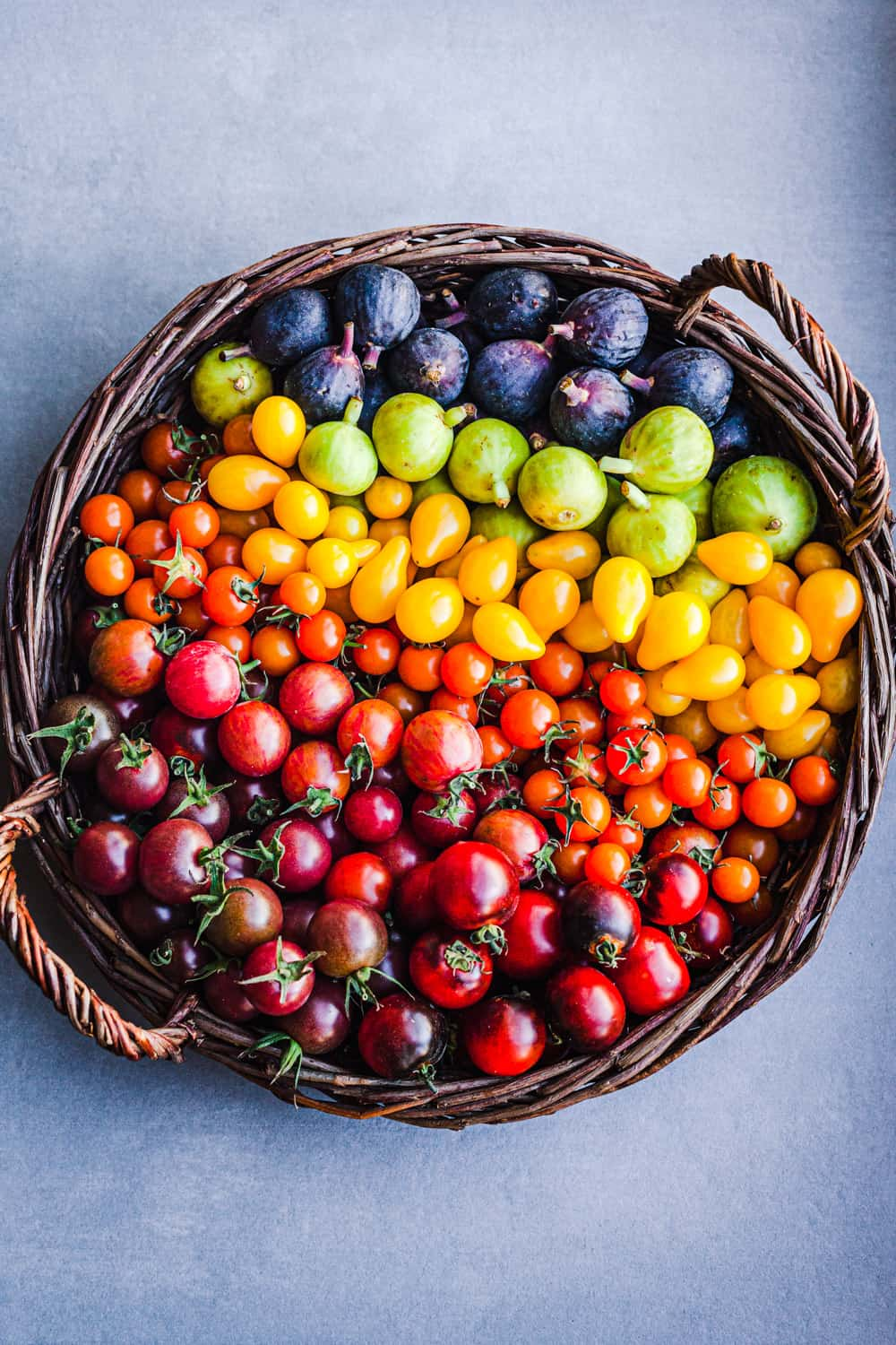 Colorful cherry tomatoes and figs in a basket.