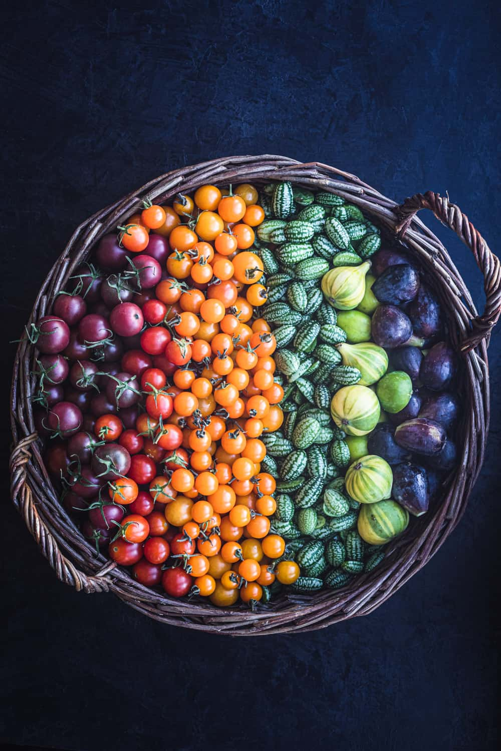 basket filled with farmers market tomatoes, cucamelons and figs