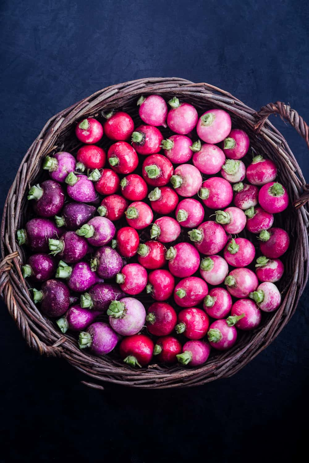 basked filled with red, purple and pink radishes, overheard shot