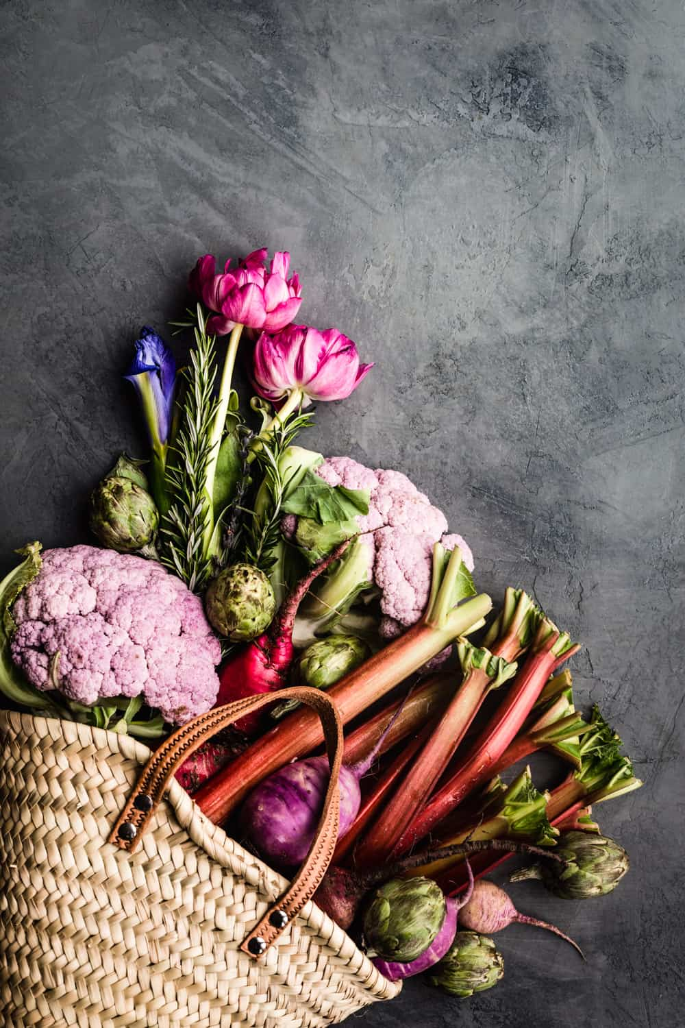 basket filled with farmers market produce; rhubarb, cauliflower, radishes, artichokes, flowers and rosemary.