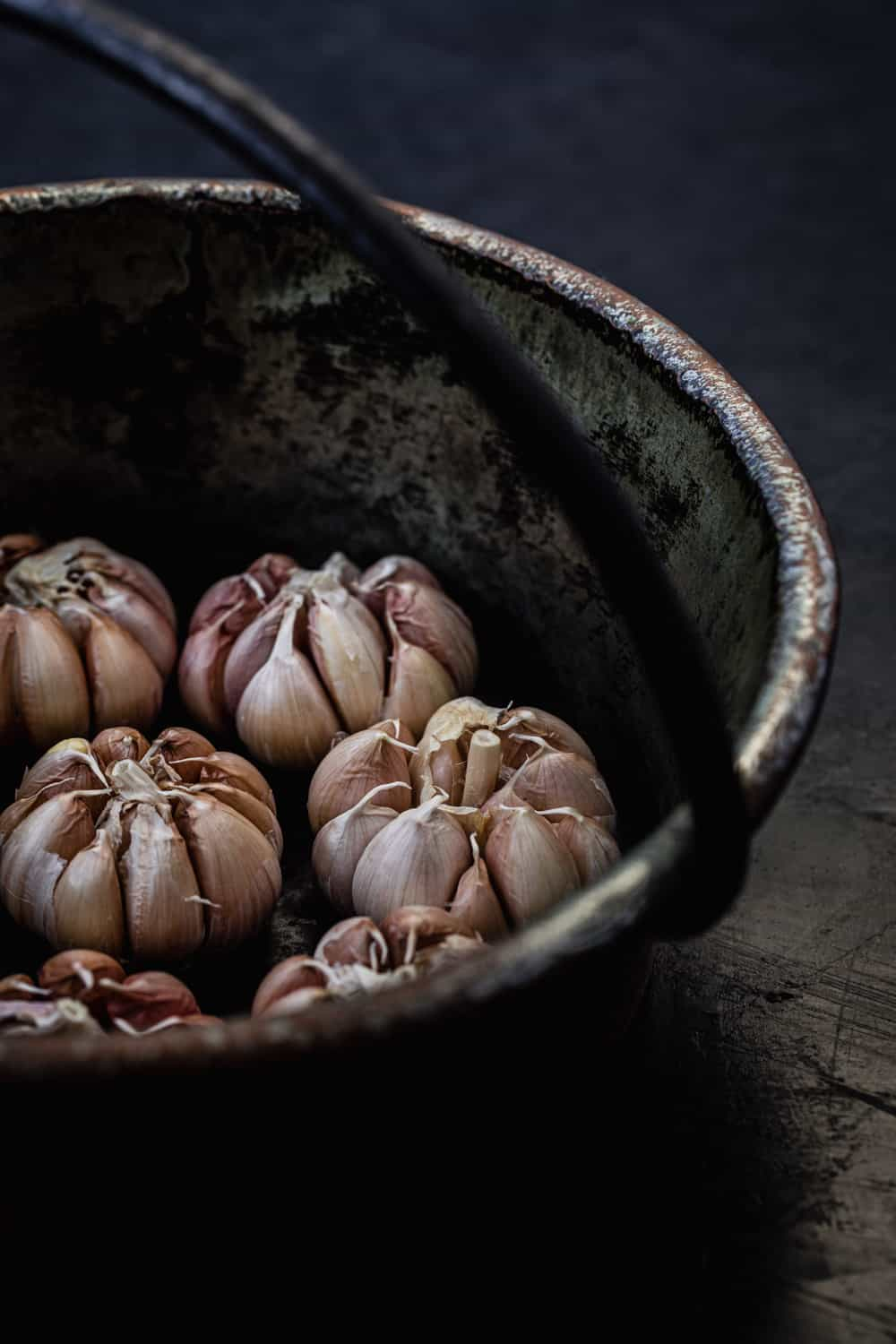 Ingredient shot of full heads of raw garlic in a pot, side angle.