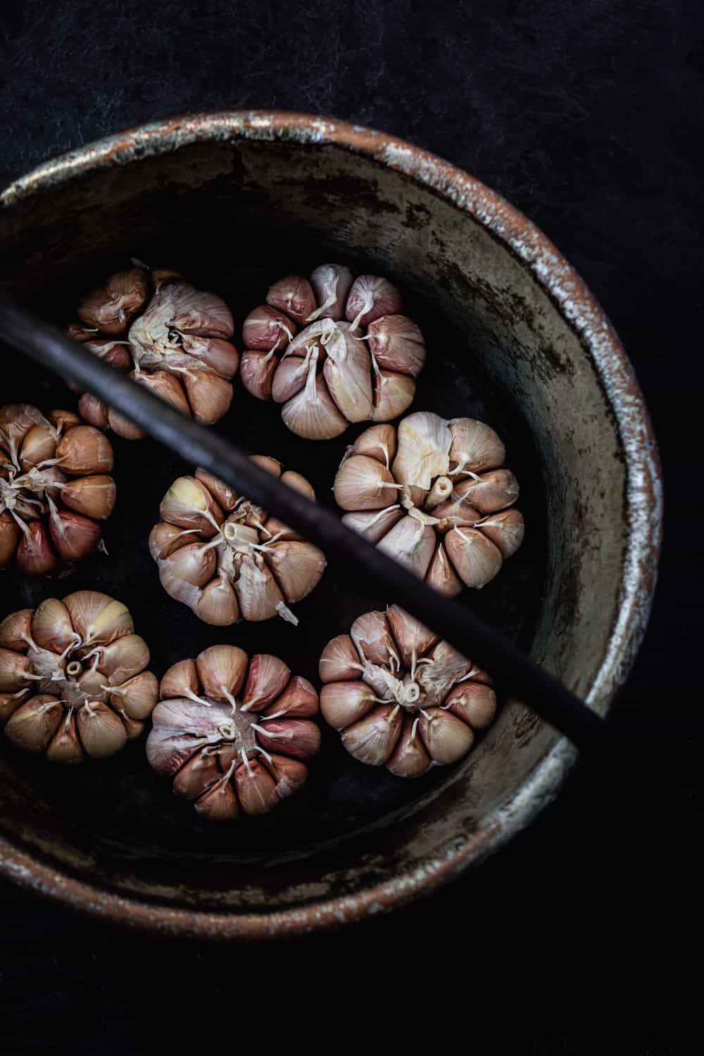Overhead shot of full heads of raw garlic in a copper pot.