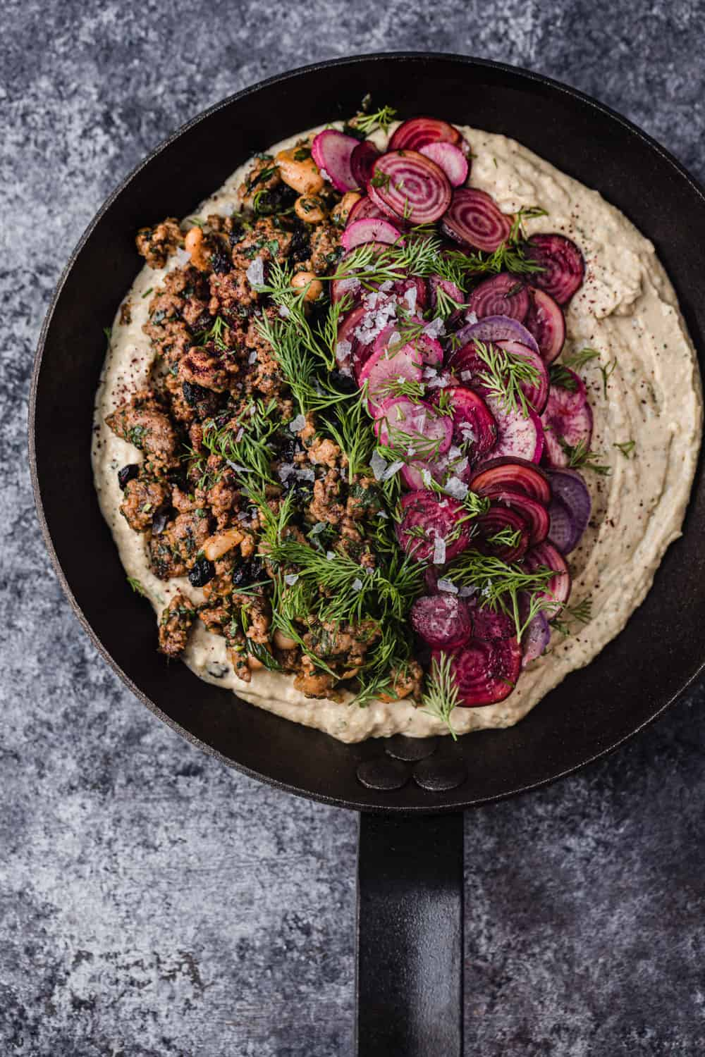 overhead shot of hummus topped with warm spiced lamb, dill, pine nuts and currants.