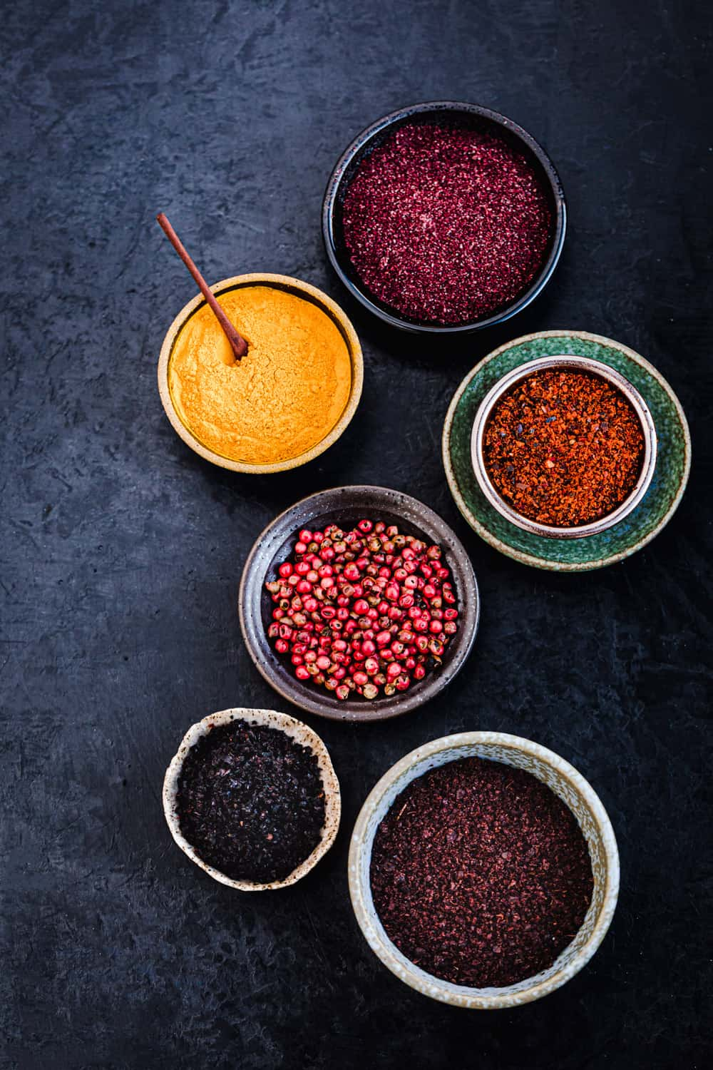 ingredient shot of 6 spices in little bowls on a black background