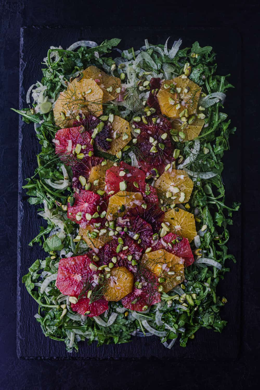 Overhead shot of orange and fennel salad on a black slate on a black background