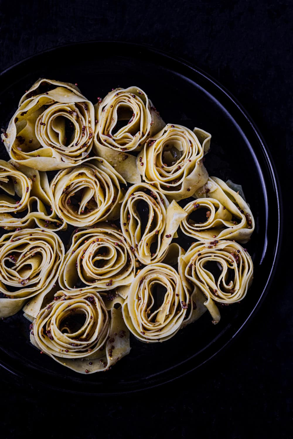 in process shot of the pappardelle on a black plate and a black background, overhead shot