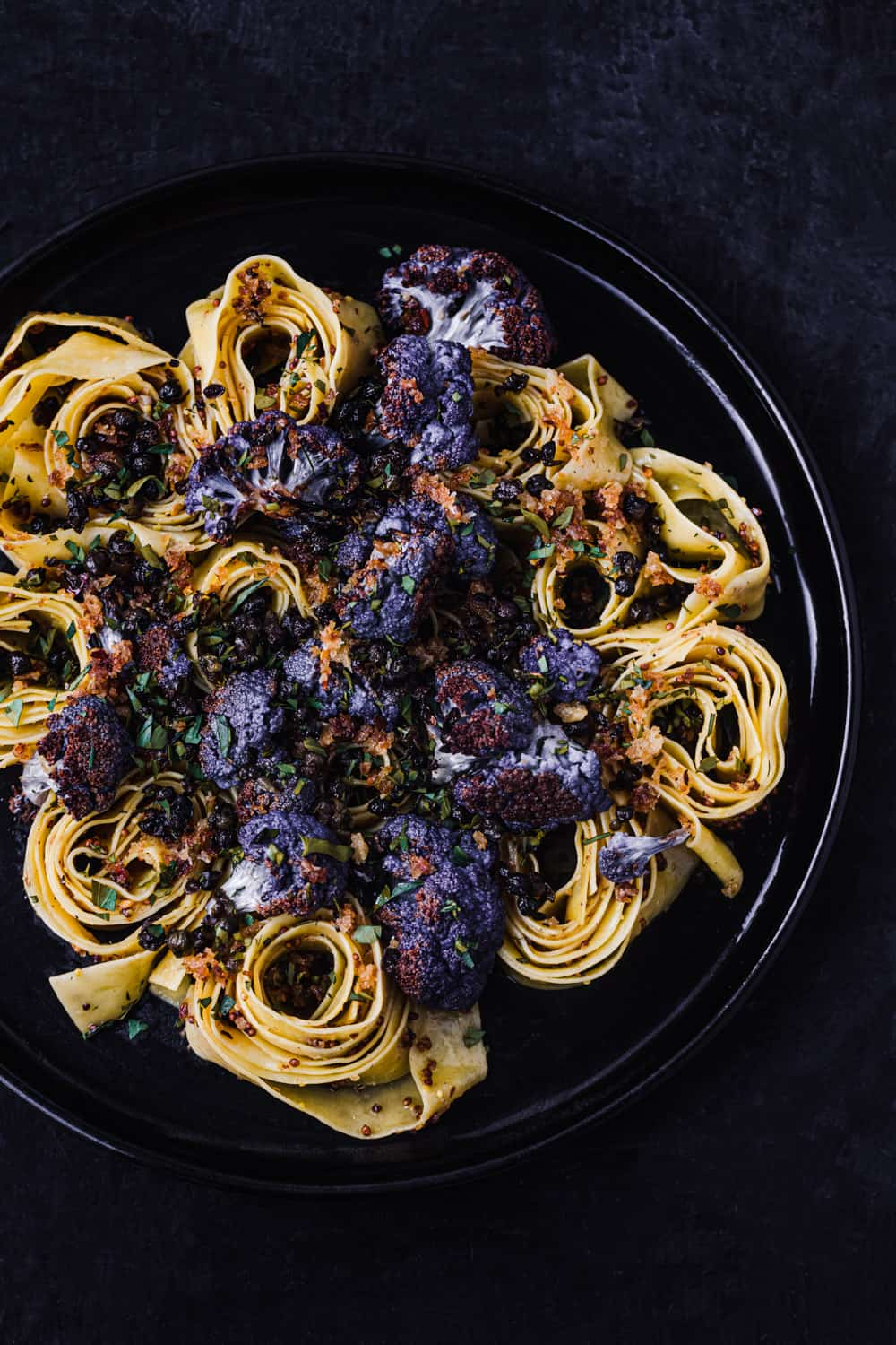 Garlicky Pasta with Cauliflower, Capers Breadcrumbs and a Mustard Brown Butter Pan Sauce, overhead shot on a dark background