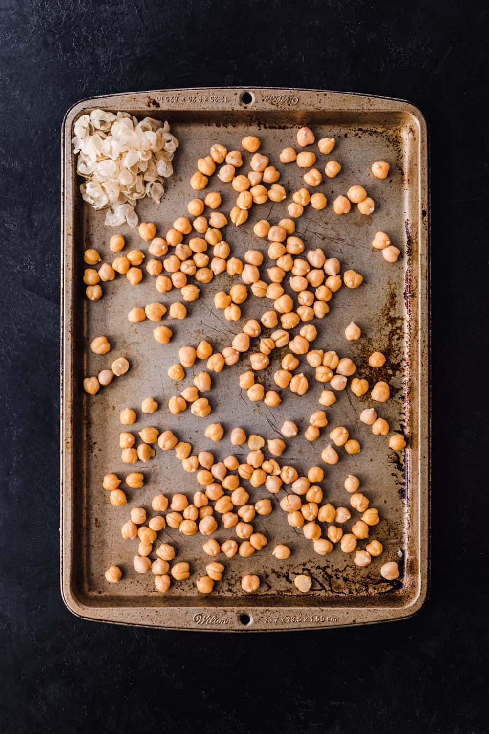 chickpeas on a sheet pan, with their skins together in a clump so you can see what the skins look like