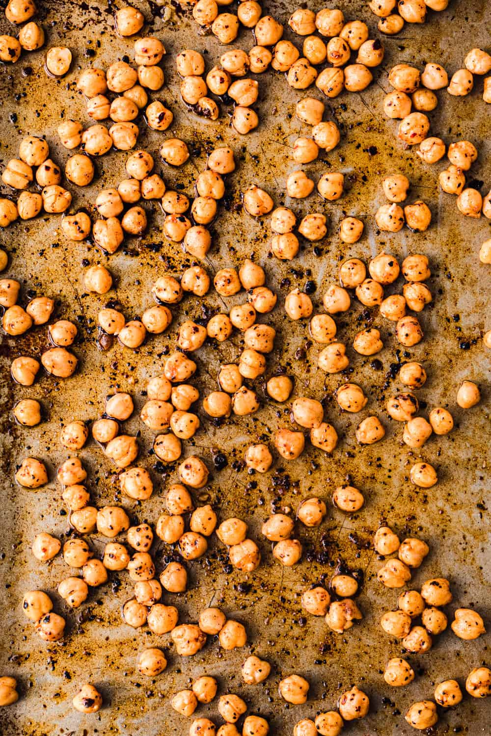 chickpeas, also called garbanzo beans, with cumin, smoked paprika, urfa chili, sumac, salt and olive oil and a cookie sheet, pre-oven.