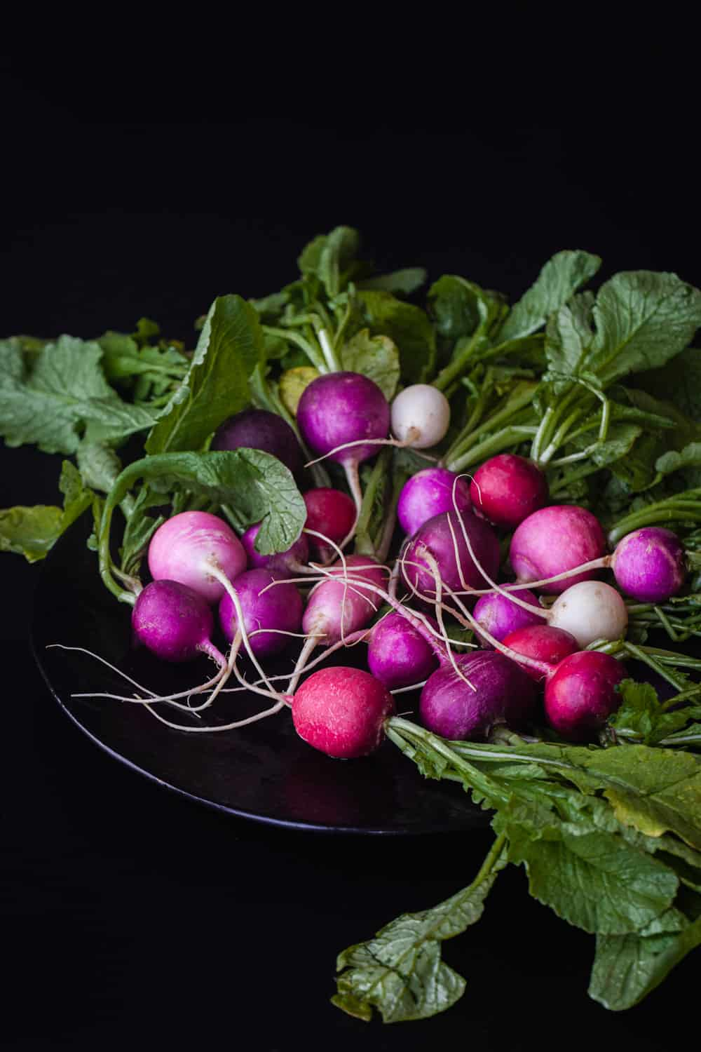 a bunch of raw round radishes on a black plate, the classic radish variety found at most supermarkets.
