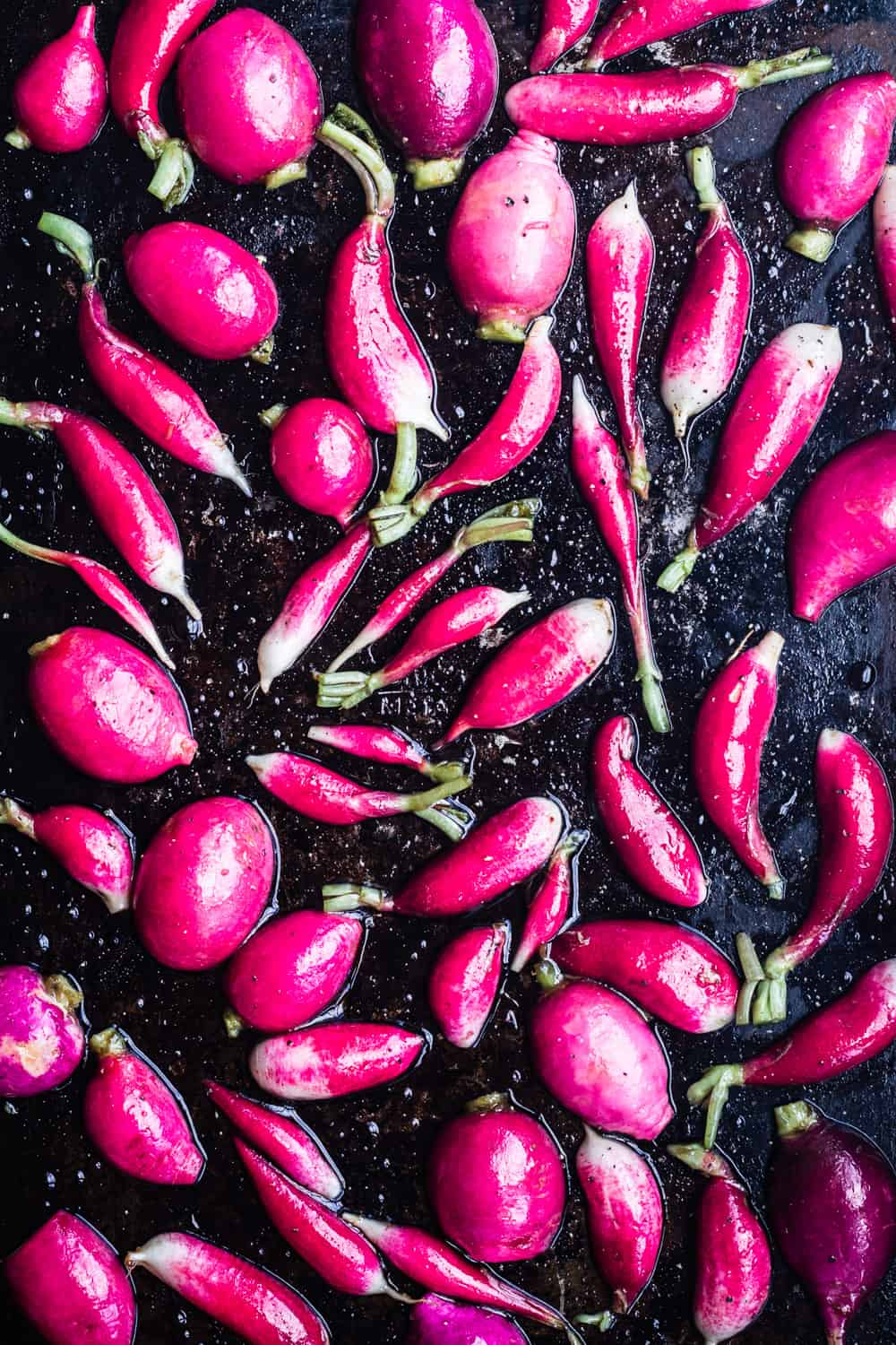 Up-close pink and French breakfast radishes, cut in half, on a baking sheet, cut-side down, pre-oven