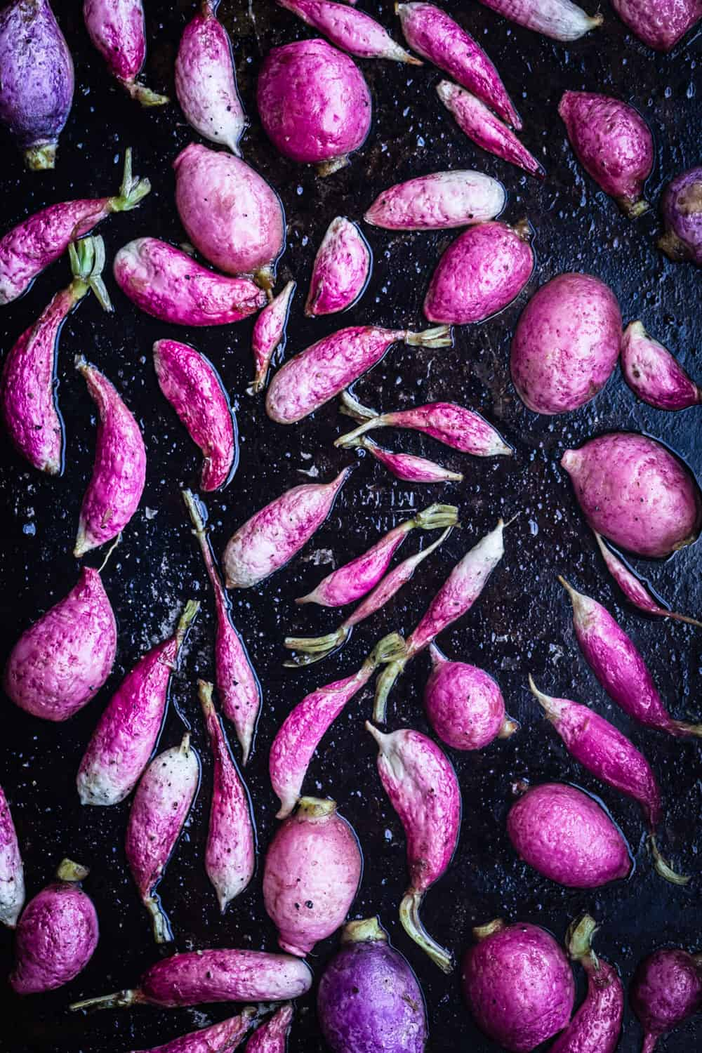 Up-close pink and French breakfast radishes, cut in half, on a baking sheet, cut-side down, post-oven